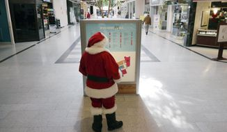 The Berkshire Mall Santa looks at the mall map kiosk to do some shopping of his own, Thursday Nov. 20, 2014, in Lanesborough, Mass. Retailers are preparing for black Friday and the kickoff of the holiday season. (AP Photo/The Berkshire Eagle, Ben Garver)