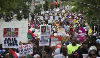 In this Aug. 23, 2014, file photo, demonstrators march to protest the death of Eric Garner in the Staten Island borough of New York. An attorney for Officer Daniel Pantaleo, a New York City police officer involved in the chokehold death of Garner, said he spent about two hours on Friday, Nov. 21, 2014, giving his account of the videotaped death of Garner to a grand jury. (AP Photo/John Minchillo, File)