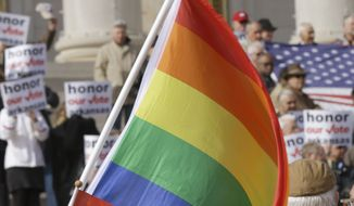 In this photo taken Nov. 19, 2014, a multi-colored flag is waved by a counter demonstrator at a rally by supporters of Arkansas' law banning same sex marriage at the Arkansas state Capitol in Little Rock, Ark. Judges in two Arkansas courtrooms are reviewing challenges to the state's gay-marriage ban. (AP Photo/Danny Johnston)