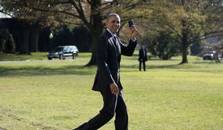 President Barack Obama holds up his BlackBerry after he forgot it and returned back to the White House to retrieve it before his departure on the South Lawn of the White House in Washington, Friday, Nov. 21, 2014, to Andrews Air Force Base, Md. Obama is traveling to Las Vegas to promote an executive order that would offer temporary legal status to millions of immigrants who are in the country illegally and set off a new fight with Republicans in Congress.(AP Photo/Pablo Martinez Monsivais)