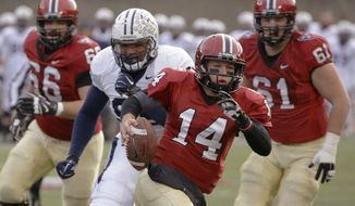Harvard quarterback Conner Hempel (14) scrambles out of the pocket on a keeper during the first half of an NCAA college football game against Yale at Harvard Stadium Saturday, Nov. 22, 2014 in Cambridge, Mass. Harvard defeated Yale 31-24 to remain undefeated and win the Ivy League Championship. (AP Photo/Stephan Savoia)