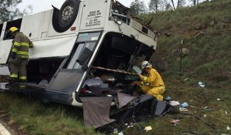 Emergency personnel check a tour bus that had already crashed earlier in the day overturned just off Interstate 5 in Northern California, killing one person and sending dozens to hospitals near the Pollard Flat area in Redding, Calif., Sunday, Nov. 23, 2014.  (AP Photo/The Record Searchlight, Alayna Shulman)