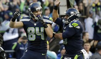 Seattle Seahawks tight end Cooper Helfet (84), left, celebrates with quarterback Russell Wilson, right, after scoring a touchdown against the Arizona Cardinals in the second half of an NFL football game, Sunday, Nov. 23, 2014, in Seattle. (AP Photo/Elaine Thompson)