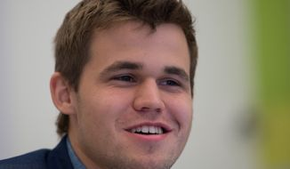 Norway's Magnus Carlsen smiles after his victory in 11th game over India's former World Champion Vishwanathan Anand, at the FIDE World Chess Championship Match in Sochi, Russia, Sunday. (AP Photo/Artur Lebedev)