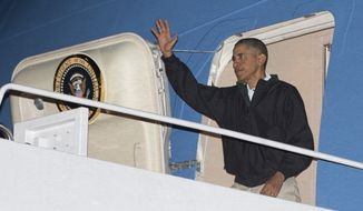 President Barack Obama waves as he deplanes from Air Force One, Sunday, Nov. 23, 2014, in Andrews Air Force Base, Md., as he returns form Las Vegas. (AP Photo/Carolyn Kaster)
