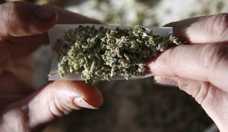 In this photo made Friday, Nov. 21, 2014,  former U.S. Marine Sgt. Ryan Begin rolls a medical marijuana joint at his home in Belfast, Maine. The Pine Tree State might be high on marijuana in 2016, sparking a charge toward legalization that has previously been the province of western states. (AP Photo/Robert F. Bukaty) ** FILE **
