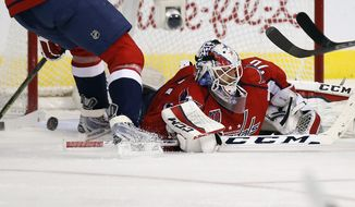 The wining goal by Buffalo Sabres center Torrey Mitchell gets past Washington Capitals goalie Braden Holtby (70) in the third period of an NHL hockey game, Saturday, Nov. 22, 2014, in Washington. The Sabres won 2-1. (AP Photo/Alex Brandon)