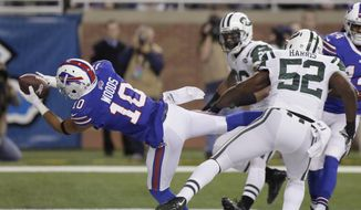 Buffalo Bills wide receiver Robert Woods (10), defended by New York Jets inside linebacker David Harris (52), scores on a seven yard reception during the first half of an NFL football game in Detroit, Monday, Nov.24, 2014. (Associated Press)