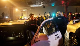 Jihab Khayyam, of St. Louis, left, gets out of his car and honks his horn to show solidarity with demonstrators as they march through traffic protesting the August shooting of Michael Brown, Sunday, Nov. 23, 2014, in St. Louis. (AP Photo/David Goldman)