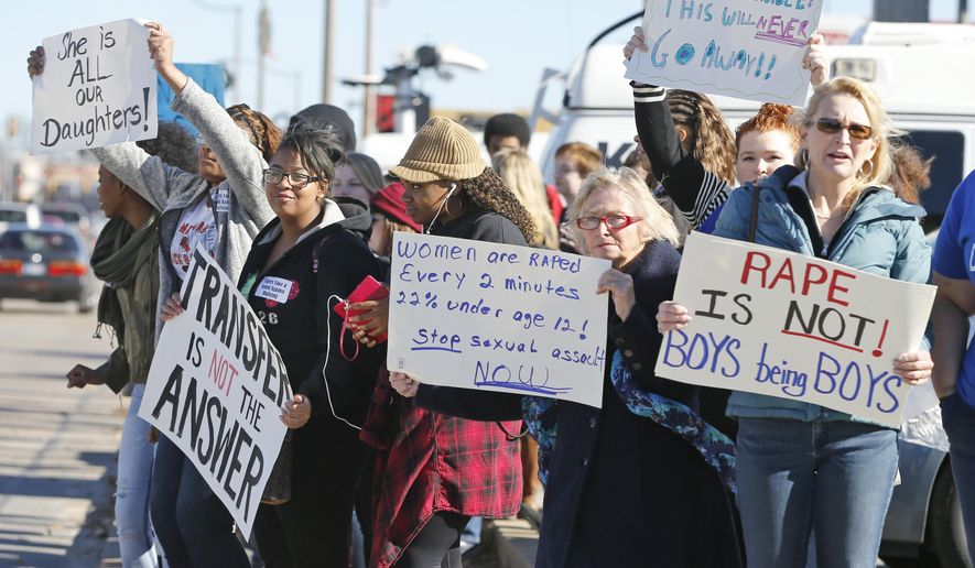 Students, parents and grand-parents hold signs during a protest across the street from Norman High School in Norman, Okla., Monday, Nov. 24, 2014. Allegations by three girls at  the high school who say they were raped by the same male student have led to a police investigation and protests by students who say school officials have mishandled the case and subsequent bullying. (AP Photo/Sue Ogrocki)