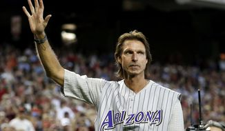 Former Arizona Diamondbacks pitcher Randy Johnson waves to the crowd during ceremonies commemorating the 10th anniversary of Johnson's perfect game prior to a baseball game between the Diamondbacks and the Los Angeles Dodgers on Sunday, May 18, 2014, in Phoenix. (AP Photo/Ross D. Franklin)