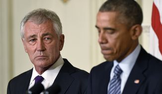 Defense Secretary Chuck Hagel, left, listens as President Barack Obama, right, talks about Hagel's resignation in the State Dining Room of the White House on Monday. (Associated Press)