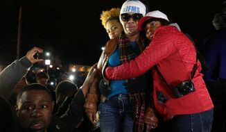 Lesley McSpadden, second from right, Michael Brown's mother, is comforted outside the Ferguson police department as St. Louis County Prosecutor Robert McCulloch conveys the grand jury's decision not to indict Ferguson police officer Darren Wilson in the shooting death of her son, Monday, Nov. 24, 2014, in Ferguson, Mo. (AP Photo/St. Louis Post-Dispatch, Robert Cohen) EDWARDSVILLE INTELLIGENCER OUT; THE ALTON TELEGRAPH OUT