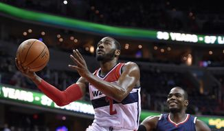 Washington Wizards guard John Wall (2) goes to the basket past Atlanta Hawks forward Paul Millsap (4) during the first half of an NBA basketball game, Tuesday, Nov. 25, 2014, in Washington. (Associated Press)