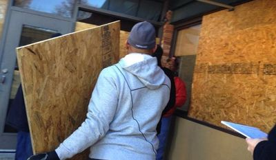 Former NFL cornerback Aeneas Williams snapped into action Tuesday by repairing storefronts damaged by rioters the night before in Ferguson, Missouri. (Twitter/Aeneas Williams)