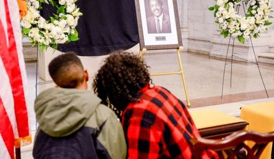 British Bostic who lives in Southeast and her son Cking, 8, stop by the Wilson Building to sign an official Book of Condolence for Councilmember and former 4-term Mayor Marion Barry who passed away Sunday at age 78, Washington, D.C., Tuesday, November 25, 2014. (Andrew Harnik/The Washington Times)