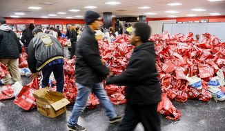 People arrive to pick out their frozen turkeys that sit piled high on the ground at Marion Barry's annual turkey giveaway held at Union Temple Baptist Church in Anacostia, Washington, D.C., Tuesday, November 25, 2014. Barry, the former 4-term Mayor of D.C. and former Councilmember, died Sunday morning at age 78. (Andrew Harnik/The Washington Times)