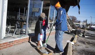 Sharon Otis, left, and her son Jonathan Johnson, 16, both of Ferguson, Mo., help clean up a strip mall after it was damaged in last night's riots, Tuesday, Nov. 25, 2014, in Ferguson, Mo. (AP Photo/David Goldman)