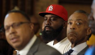 Michael Brown Sr., center, listens along side Rev. Al Sharpton, right, as Brown family attorney Anthony Gray, left, speaks during a news conference at Greater St. Mark Church Tuesday, Nov. 25, 2014, in St. Louis County, Mo. Rioting broke out Monday after a grand jury decided not to indict a white Ferguson police officer in the shooting death of the unarmed, black 18-year-old Michael Brown. (AP Photo/Jeff Roberson)