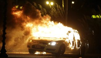 A police car is set on fire after a group of protesters vandalize the vehicle following the announcement of the grand jury decision in Ferguson, Missouri. A grand jury has decided not to indict Ferguson police officer Darren Wilson in the death of Michael Brown, the unarmed, black 18-year-old whose fatal shooting sparked sometimes-violent protests. (AP Photo/Charlie Riedel)