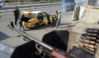 In this Saturday, Nov. 22, 2014, photo, Iraqi federal policemen search a car at a checkpoint in Baghdad, Iraq. The government is now trying to revamp security measures, moving away from reliance on ubiquitous concrete blast walls and police checkpoints. Instead, the plan is to beef up police intelligence units that have gone understaffed and underfunded since the fall of Saddam Hussein. (AP Photo/Karim Kadim)