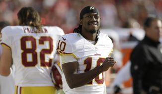 Washington Redskins quarterback Robert Griffin III (10) stands on the sideline during the second quarter of an NFL football game against the San Francisco 49ers in Santa Clara, Calif., Sunday, Nov. 23, 2014. (AP Photo/Ben Margot)