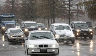 Vehicles cruise under light snowfall, Wednesday, Nov. 26, 2014, in Newark, N.J. The northern New Jersey region is expected to be hit by a snowstorm, which will cause problems for those traveling ahead of the Thanksgiving Day holiday. (AP Photo/Julio Cortez)