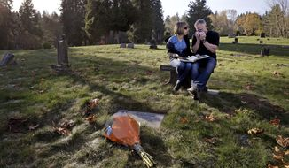 "ADVANCE FOR USE FRIDAY, NOV. 28, 2014, AND THEREAFTER- In this Nov. 17, 2014 photo, Rob Robertson wipes away tears as he sits with his wife Linda while they visit the grave of their son, Ryan, in Issaquah, Wash. The couple, evangelical Christians, brought their son to ""reparative therapy"" when he came out to them as gay. His sexual orientation didn't change, and he became addicted to drugs and eventually died of an overdose. The Robertsons are now dedicated to helping other evangelical parents accept their gay children. (AP Photo/Elaine Thompson)"