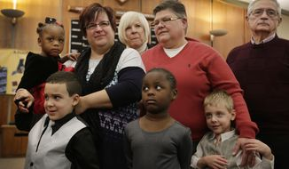 April DeBoer, center left, and Jayne Rowse, center right, attend Michigan Adoption Day with their family to finalize their adoption of 2-year-old Rylee DeBoer-Rowse, left, at the Oakland County Court House in Pontiac, Mich., on Nov. 25, 2014. The Detroit-area nurses are challenging Michigan's ban on gay marriage. Their family, from left are, Rylee, Nolan, 5, Ryanne , 4, and Jacob, 5. In the back are April DeBoer's parents Wendy DeBoer and Ken DeBoer, right. (AP Photo/Detroit Free Press, Mandi Wright)