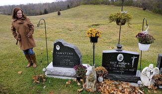 In this Nov. 7, 2014 photo, Debbie Larsen views the graves of her sister Linda Sawatzke and nephew Rory Gavic at the St. Francis Catholic Cemetery near Buffalo, Minn. Gavic was a young, decorated military member who served his country overseas twice, who had earned praise and the respect of his peers, who had volunteered as a Big Brother. His suicide in 2009 devastated his family, especially his mother Linda Sawatzke who killed herself four years later with the same handgun. (Associated Press/The St. Cloud Times, Dave Schwarz) **FILE**
