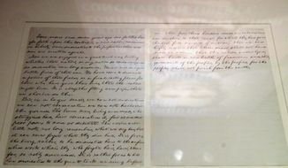 """In this Nov. 21, 2014, photo provided by The Abraham Lincoln Presidential Library and Museum, an image of Abraham Lincoln reflects off a case holding one of the five existing handwritten copies of the Gettysburg Address at the Library and Museum in Springfield, Ill. The address is part of """"Undying Words: Lincoln 1858-1865"""" a new exhibition at the presidential library on Lincoln's greatest speeches. (AP Photo/Courtesy The Abraham Lincoln Presidential Library and Museum, Christopher Wills)"""