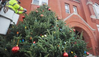 In this Tuesday, Nov. 25, 2014 photo, Greg Pinion decorates a Christmas tree outside of City Hall in Oxford, Miss. The city will hold a ceremonial tree lighting on Friday evening. (AP Photo/Oxford Eagle, Bruce Newman)