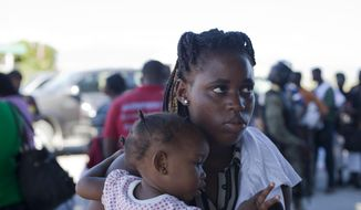 "Youtchike Dormeus, 18, a repatriated Haitian, holds her one-year-old daughter Chemael Jean, as she is interviewed after landing at the Toussaint Louverture International Airport in Port-au-Prince, Haiti, Wednesday, Nov. 26, 2014. The Bahamas aims to become less hospitable to its swelling population of migrants lacking legal status with new immigration rules took effect Nov. 1. ""In the Bahamas, they treat Haitians like dogs,"" Youchike Dormeus, an 18-year-old deportee, said as she got off the plane in Port-au-Prince. The country, which denies treating anyone inhumanely, has deported 3,000 people this year. (AP Photo/Dieu Nalio Chery)"