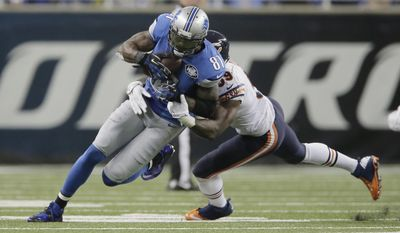 Detroit Lions wide receiver Calvin Johnson (81) is tackled by Chicago Bears inside linebacker Christian Jones (59) after his 9-yard reception during the first half of an NFL football game in Detroit, Thursday, Nov. 27, 2014. With this catch, Johnson set a new NFL record for fewest games (115) to reach 10,000 career receiving yards. (AP Photo/Duane Burleson)
