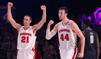 Wisconsin's Josh Gasser (21) and Frank Kaminsky (44) celebrate their victory over Georgetown in the Battle 4 Atlantis basketball tournament in Paradise Island, Bahamas, Thursday Nov. 27, 2014. (AP Photo/Tim Aylen)