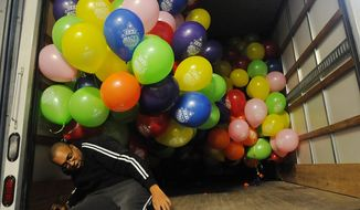 Balloon crewman Kevin Jackson, of Life O' The Party in Hackensack, N.J., gets out Wednesday, Nov. 26, 2014, from under some of the balloons that are part of the 15,000 Macy's balloons for the parade and will transport them to New York. (AP Photo/Northjersey.com, Mitsu Yasukawa)