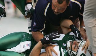 FILE - In this Sunday, Nov. 6, 2005, file photo, New York Jets' Wayne Chrebet lies unconscious while a San Diego Chargers trainer looks over him after he took a hit on a reception during the fourth quarter of an NFL football game, in East Rutherford, N.J. Chrebet sustained a season-ending concussion on the play. Chrebet suffered at least six or seven concussions during his career. At halftime of the Jets' game against Miami, on Monday, Dec. 1, 2014, Chrebet will be inducted into the team's Ring of Honor along with late former owner Leon Hess. (AP Photo/Tim Larsen, File)