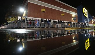 Shoppers line up outside a Best Buy in Dartmouth, Mass., early Friday, Nov. 28, 2014, on a rainy day while waiting for the store to open at 1 a.m. (AP Photo/The Standard-Times, Peter Pereira)