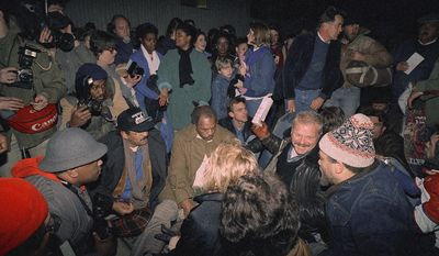 """Marion Barry, center, and actors Brian Dennehy, second from right, and Martin Sheen, standing at right, gather on Capitol Hill in 1987 to dramatize the """"homeless crisis"""" at the Grate American Sleep Out. (AP Photo/Dennis Cook)"""