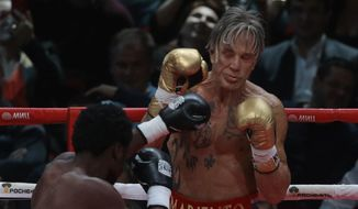 Actor Mickey Rourke, right, holds up his guard against his opponent Elliot Seymour of the United States, during their professional boxing match, at the Luzhniki Stadium, Moscow, Friday, Nov, 28, 2014. Rourke returned to the boxing ring Friday at the age of 62, defeating a fighter less than half his age in an exhibition bout. (AP Photo/Ivan Sekretarev)