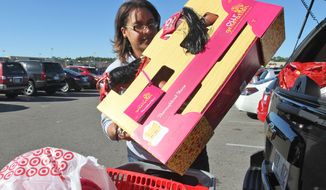 Jennifer Jenkins of D'Iberville, Miss., loads toys into her car after Black Friday shopping at Target in The Promenade shopping center in D'Iberville on Friday Nov. 28, 2014. Jenkins was buying gifts paid for by employees of the Orange Grove Urgent Care to donate to a church for distribution. (AP Photo/Sun Herald, John Fitzhugh)
