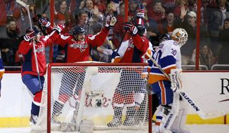 Washington Capitals left wing Alex Ovechkin, second from left, from Russia, celebrates his goal with center Nicklas Backstrom, left, from Sweden, and right wing Tom Wilson, with New York Islanders goalie Chad Johnson (30) nearby in the second period of an NHL hockey game, Friday, Nov. 28, 2014, in Washington. (AP Photo/Alex Brandon)