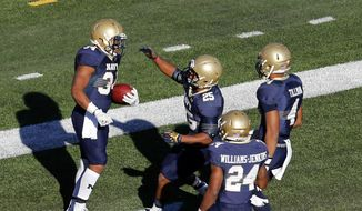 Navy running back Demond Brown (25), running back Ryan Williams-Jenkins (24) and wide receiver Jamir Tillman (4) congratulate fullback Noah Copeland (34) after his touchdown against South Alabama in the first half of an NCAA college football game Friday, Nov. 28, 2014, in Mobile, Ala. (AP Photo/AL.com, Mike Kittrell) MAGAZINES OUT