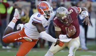 Florida State quarterback Jameis Winston (5) manages to escape a sack as he is hit by Florida defensive lineman Dante Fowler, Jr. (6) during the first half of an NCAA college football game in Tallahassee, Fla., Saturday, Nov. 29, 2014. (AP Photo/John Raoux)