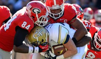 Georgia linebackers Leonard Floyd (84) and Ramik Wilson stop Georgia Tech running back Zach Laskey, center, during the first half of an NCAA college football game Saturday, Nov. 29, 2014, in Athens, Ga. (AP Photo/David Tulis)