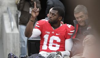 Ohio State quarterback J.T. Barrett acknowledges fans as he is driven from the field after an injury in the fourth quarter of an NCAA college football game Saturday, Nov. 29, 2014, in Columbus, Ohio. Ohio State beat Michigan 42-28. (AP Photo/Jay LaPrete)