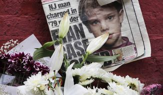 This May 28, 2012, file photo shows a newspaper with a photograph of Etan Patz that is part of a makeshift memorial in the SoHo neighborhood of New York. (AP Photo/Mark Lennihan, File)