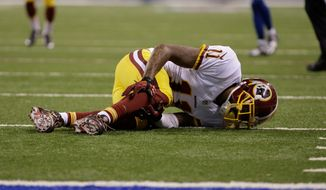 Redskins receiver DeSean Jackson grabs his leg after collapsing to the ground as he attempted to catch a pass in the third quarter. He left the game with a bruised fibia. (Associated Press)