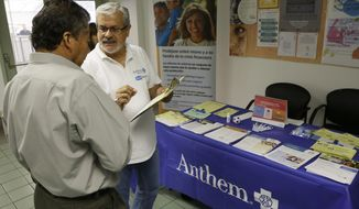 In this Oct. 1, 2013, file photo, Alberto Pizon, right, a representative of Anthem BlueCross BlueShield Latino Health Access group provides free information to Paulino Zarate, 65, left, on the new health options available during a health fair promoted at the Binational Health Week event held at the Mexican Consulate in Los Angeles. (AP Photo/Damian Dovarganes, File)