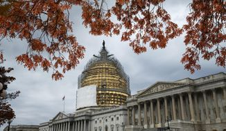 This Nov. 13, 2014, file photo shows the U.S. Capitol Dome, in Washington, surrounded by scaffolding for a long-term repair project, and framed by the last of autumn's colorful leaves. (AP Photo/J. Scott Applewhite, File)
